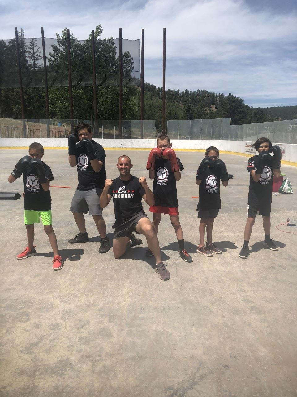 boxing students and instructors posing on hockey rink