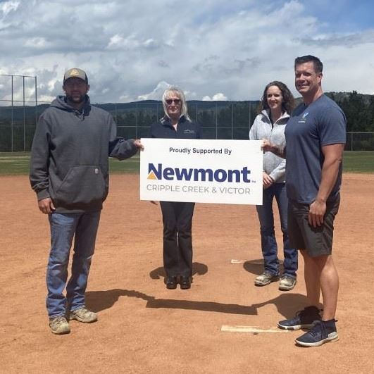 "Photo of four adults in a baseball field holding a sign that says ""Proudly Supported by Newmont&#"